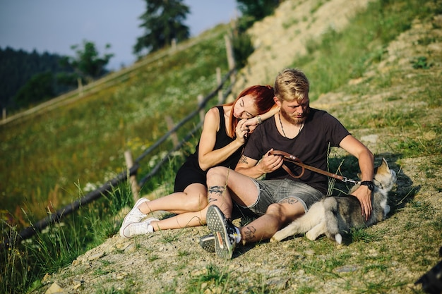 Beautiful couple sits on a hill and hugging each other