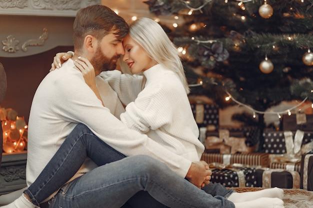 Красивая пара сидит дома возле елки