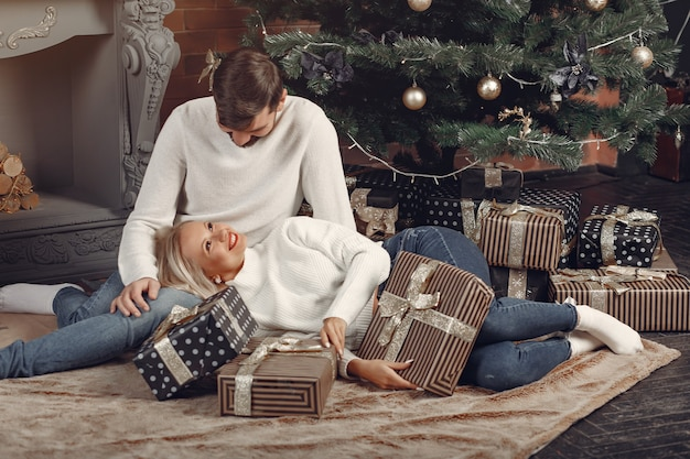 クリスマスツリーの近くに家に座っている美しいカップル
