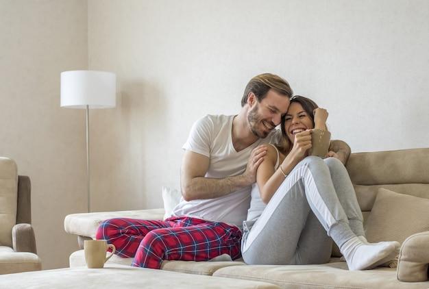 Beautiful couple sitting on a beige sofa