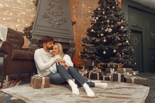 Beautiful couple sitting at home near christmas tree