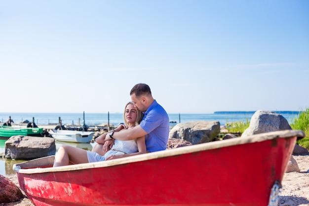 Красивая пара, сидя в старой лодке на летнем пляже