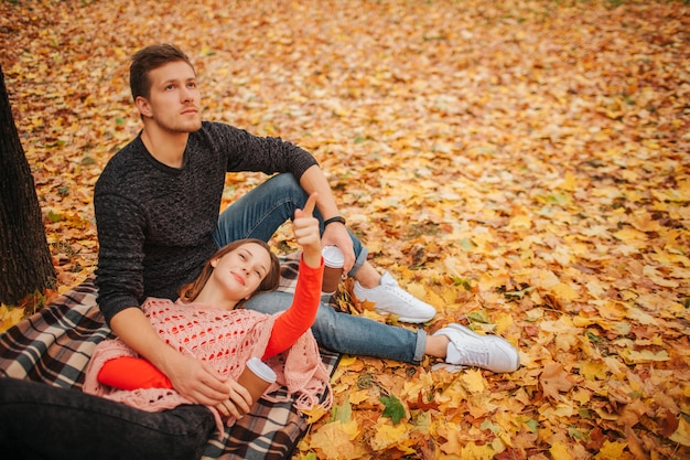 Beautiful couple sitting and lying in autumn park alone. they look in same direction. woman lying on guy's legs. guy sits on blanket. they hold cup of coffee.