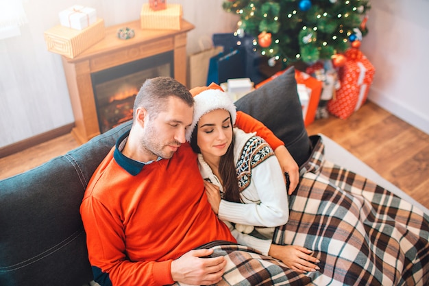 Beautiful couple sitting together on sofa. they fell asleep. he embraces her. she is leaning to him.