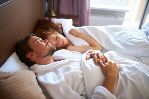 美しいカップルは家で寝る、若い白人男性と女性はベッドに横たわる