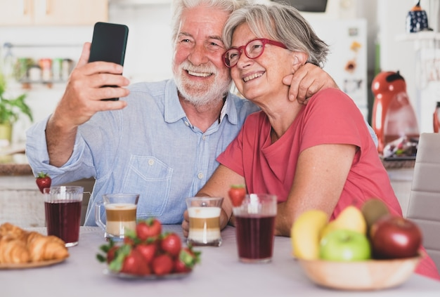 Beautiful couple smiling for a selfie, having breakfast at home. senior people relaxed and happy