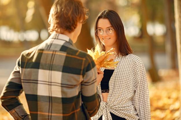 Le belle coppie trascorrono il tempo in un parco di autunno