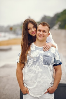 美しいカップルは秋の曇り公園で時間を過ごす