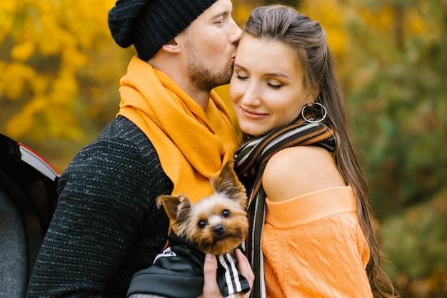 美しいカップルは犬と一緒に秋の公園で時間を過ごします