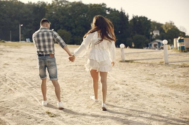 美しいカップルは夏のビーチで時間を過ごす