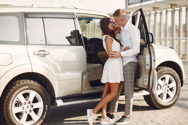 美しいカップルは車の近くの夏の公園で時間を過ごす