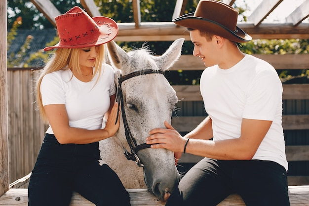 Beautiful couple spend time with a horses