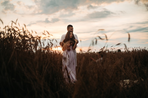 Beautiful couple standing in the field.