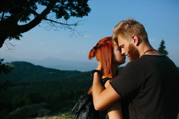 Bella coppia in piedi su una collina e che si abbraccia dolcemente