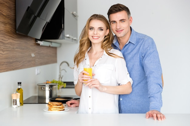 Beautiful couple standing on kitchen with pancakes and fresh orange juice for breakfast