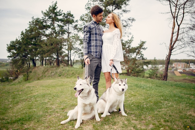 Beautiful couple in a summer forest with a dogs