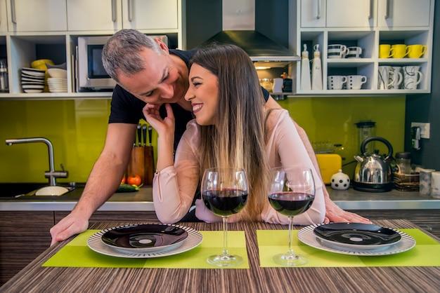 キッチンカウンターに座っている間、元の家で話している美しい夫婦。カップルは愛情のある瞬間を共有