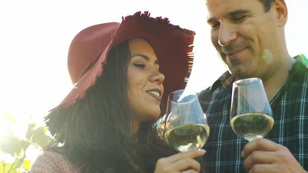 レンズフレアでワインを味わう美しいカップル。ワイン試飲会。