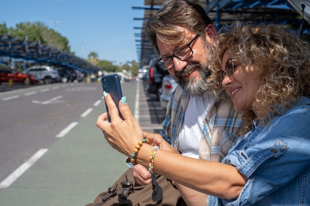 Beautiful couple of tourists in the parking of the airport looking at smart phone