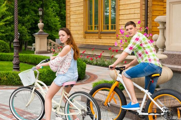 公園の高級住宅を背景に自転車に乗っている美しいカップルが振り返り、カメラをのぞき込む