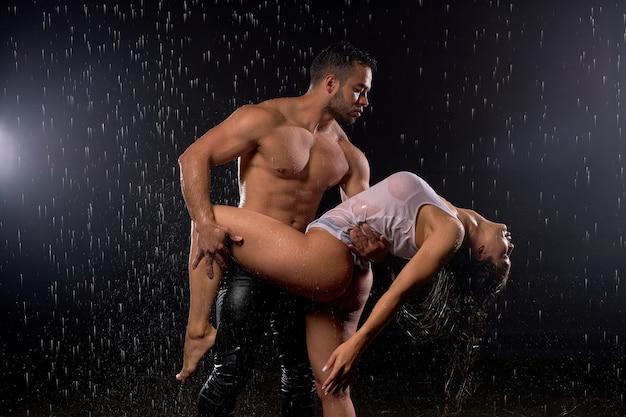 スタジオで雨の中、一緒に踊る、ロマンチックな男性と女性の美しいカップル