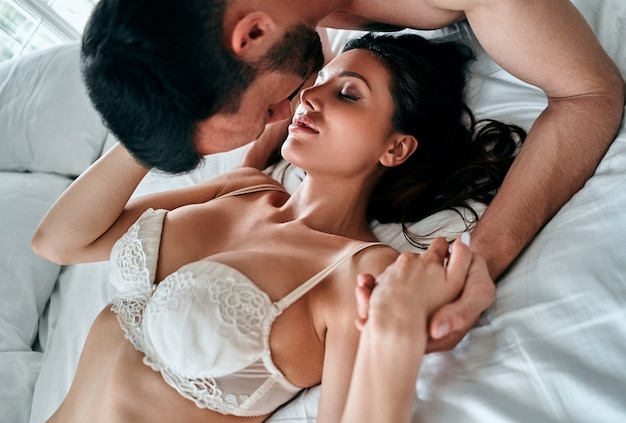 The beautiful couple in underwear kissing in the bed