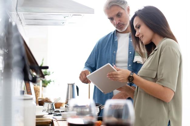 디지털 태블릿을 사용하고 집에서 부엌에서 요리하는 동안 웃고 있는 아름다운 커플