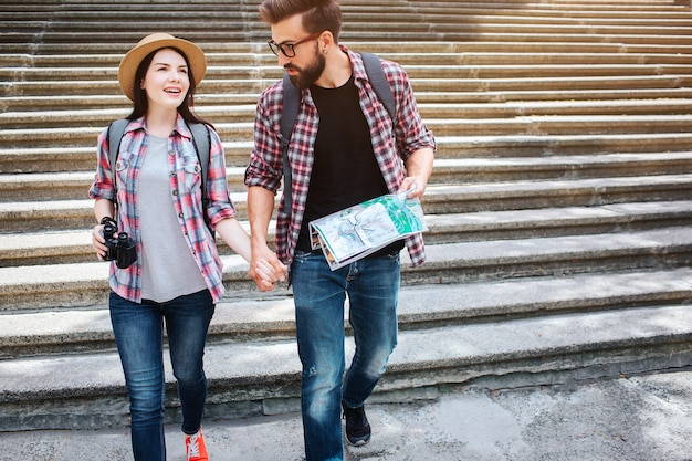 Beautiful couple walk together. they hold each other's hand. young man look at woman. he holds map. they walk on stairs.