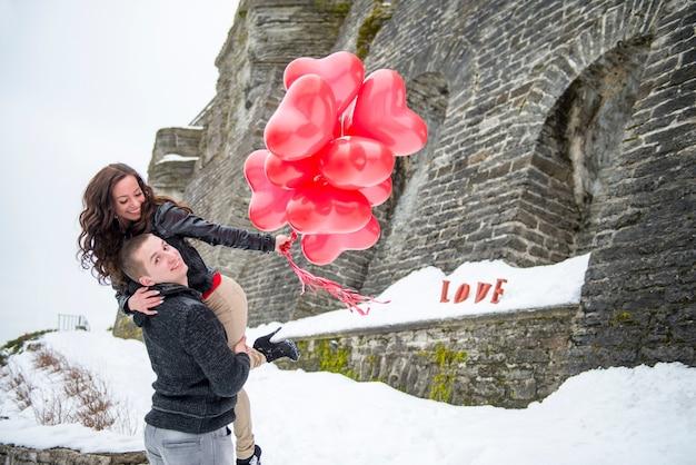 赤い風船で冬の街を歩いている美しいカップル。ヨーロッパの都市オールドタリンでの男女とのラブストーリー