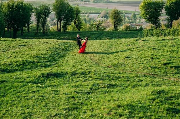 Красивая пара прогулки зеленый газон