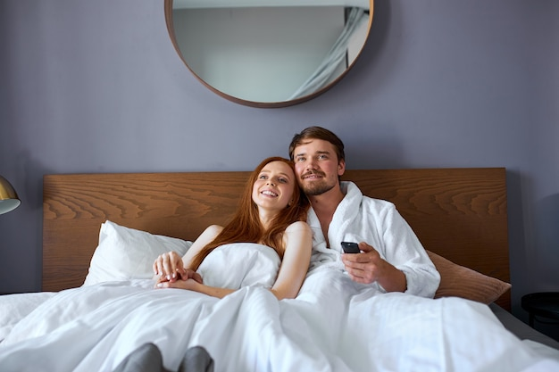 Beautiful couple watch tv on bed, have rest in hotel at weekends