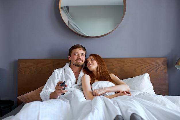 美しいカップルはベッドでテレビを見て、週末にホテルで休憩します