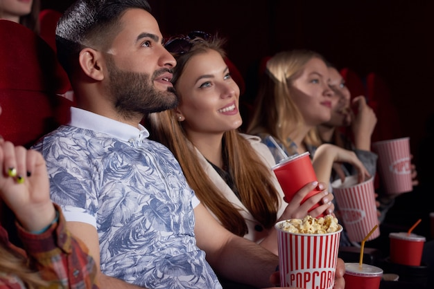 Beautiful couple watching interesting film at cinema and smiling.