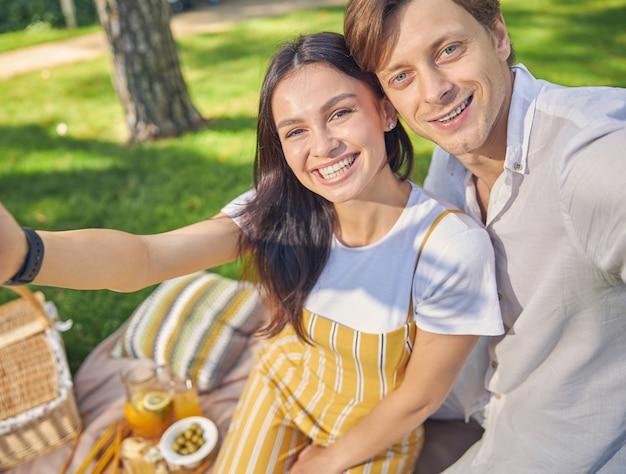 사진 카메라에 셀카를 복용 캐주얼 의류를 입고 아름다운 커플