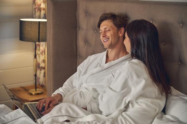 침대에 앉아 인터넷을 서핑하는 동안 자신의 침실에서 이야기하는 흰색 목욕 가운을 입고 아름다운 커플