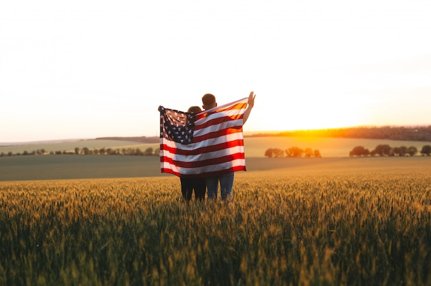 Beautiful couple with the american flag in a wheat field at sunset.  independence day, 4th of july.