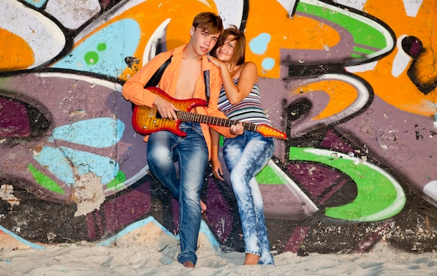Beautiful couple with guitar near graffiti wall.