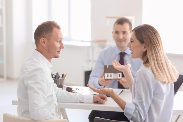 Beautiful couple with real estate agent in office