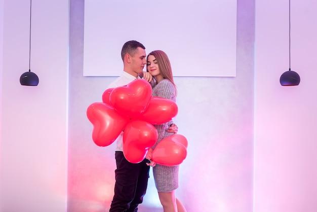 スタジオでポーズをとってバレンタインデーを祝う赤い気球と美しいカップル