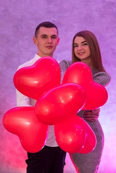 Beautiful couple with red air balloons celebrating valentine's day posing in studio