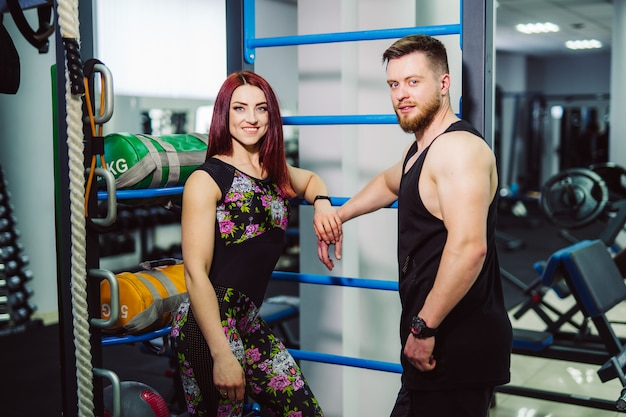 Beautiful couple with strong physical body standing in the sports club and smiling. attractive woman and muscular bodybuilder man posing in gym.