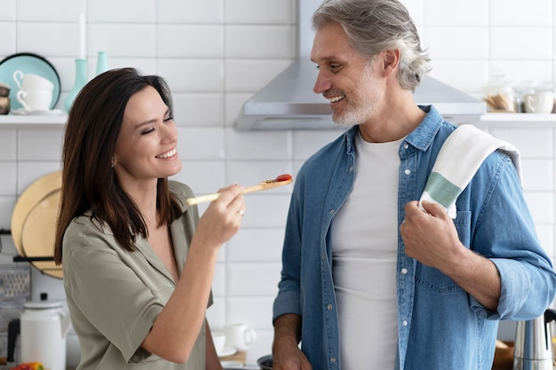 Beautiful couple. woman feeding husband and smiling while cooking in kitchen at home.