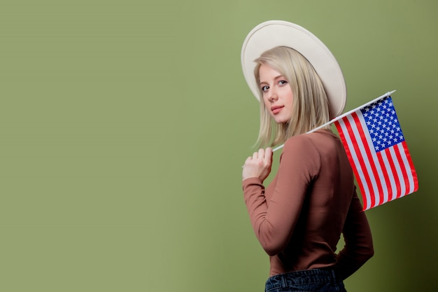 Beautiful cowgirl in a hat with united states of america flag