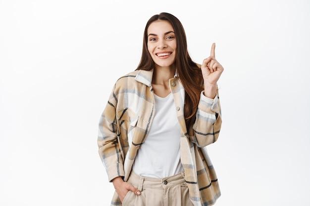 美しい恥ずかしがり屋の女性は、白い壁の上に立って、指を上に向けてクスクス笑い、かわいい笑顔、広告を表示し、上部のコピースペースに製品バナーまたは会社のロゴを示します