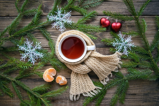 Beautiful cozy christmas picture with a mug of hot tea in a scarf with fir branches, hearts, snowflakes, tangerine on a wooden background