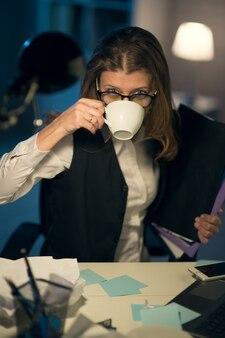残業の夜までオフィスで働くのに疲れた美しい狂気の成熟したビジネス女性workaholic