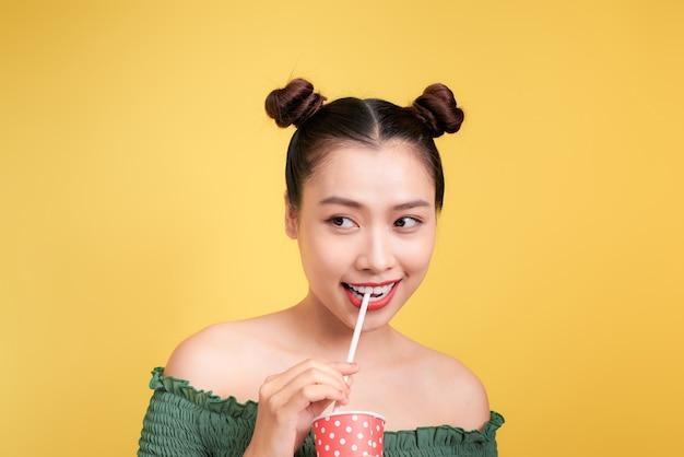 ストローでコーラを飲む赤い唇を持つ美しいクレイジー笑顔アジアの女性の女の子