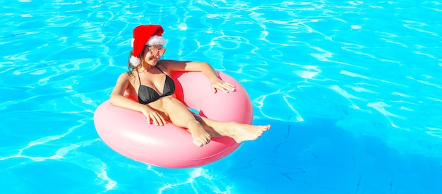 Beautiful crazy woman in christmas hat relaxing on inflatable ring in blue swimming pool. winter holiday. copy space.