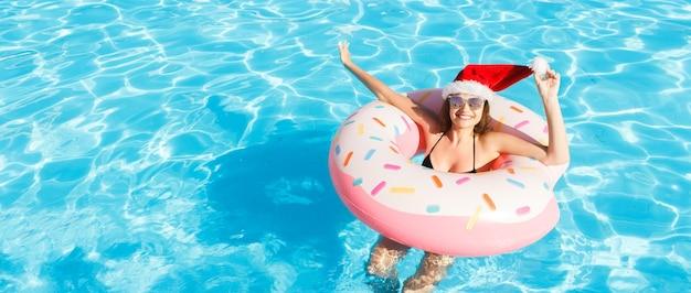 파란색 수영장에서 풍선 반지에 편안한 크리스마스 모자에 아름 다운 미친 여자. 복사 공간.