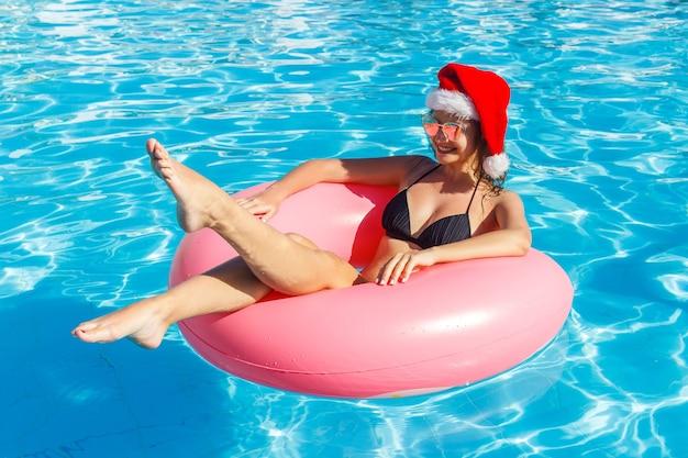파란색 수영장에서 풍선 반지에 편안한 산타 클로스 모자에 아름 다운 미친 여자